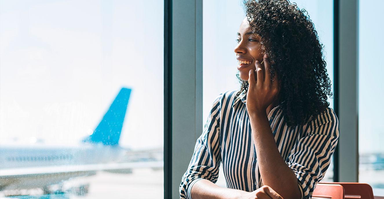 Mulher sorrindo ao telefone, com um avião ao fundo, desfocado