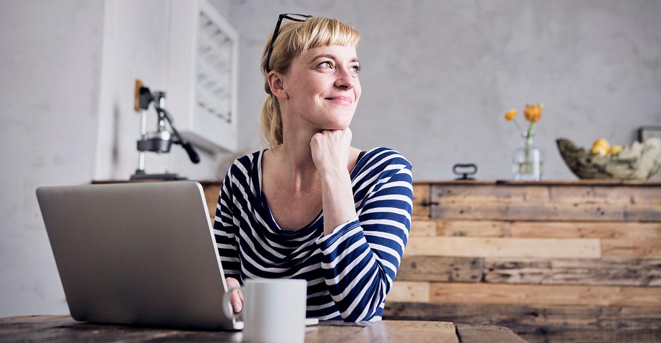 Mulher olhando para o lado, próxima ao notebook e uma caneca branca
